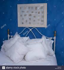 wrought iron bed with white cushions and linen in bright blue
