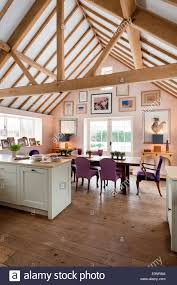 open plan kitchen diner with pitched roof and beamed ceilings the