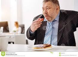 employé de bureau employé de bureau affamé drôle avalant des beignets photo stock