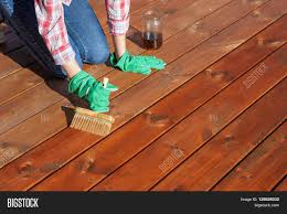 Woman Applying Protective Varnish Or Wood Oil On A Patio Wooden