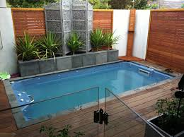 tiny pool in backyard with grass es and timber wood fences