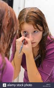 young teenage applying eyeliner makeup in the bathroom mirror