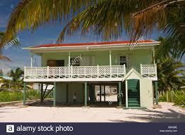 caye caulker belize wooden house on stilts on sand beach with palm
