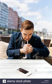 Outdoor Cafe Lighting by Young Man Waiting At Outdoor Cafe Lighting A Cigarette Stock Photo
