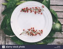 rustic christmas table setting with red berries bordering a