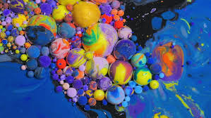 color drops floating in oil and water over a colorful underground