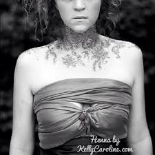 viney and floral henna tattoos on the neck and collar bone