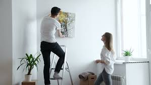 Interior Design On Wall At Home Moving House Couple Hanging Picture On Wall In New Home Stock