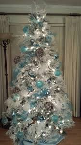 snow white flocked tree decorated with aqua blue silver