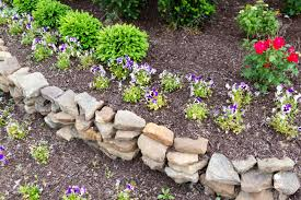 rock retaining wall in a garden with rocks and