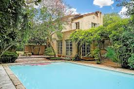 2 story beige stucco house with pool