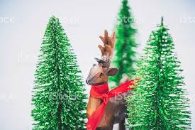 wooden deer in real snow with tiny trees in background stock photo