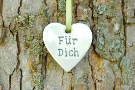 white heart hanging on tree as symbol for love and romance stock