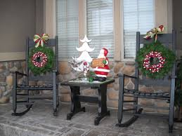 lighted garland arrangements on the white porch fences and pole