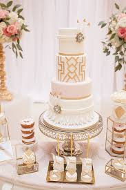 picture of a white and gold wedding cake with geo decor petals