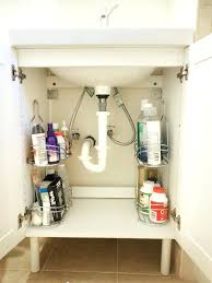 use shower caddies as shelving to organize awkward sink spaces for