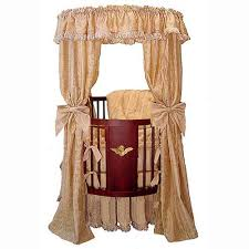 beautiful oval  round baby cribs for unique nursery decor with florentine style in cherry wood is accented with a gilded cherub on front  panel on from homestratospherecom
