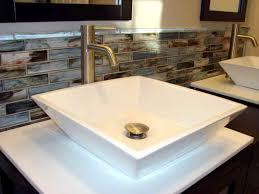 bathroom with black cabinets and mosaic backsplash tiles