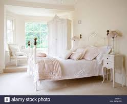pale pink silk quilt and white bedlinen on white wrought iron bed