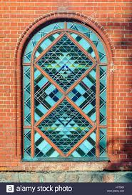 octagon stained glass window stained glass arched window in red brick wall facade front view