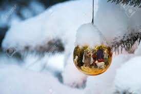 this christmas tree ornament brightly reflects a nativity scene