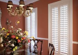 decorating charming sunburst shutters in white on orange wall