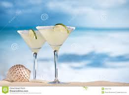 blue raspberry margarita margarita cocktail on beach blue sea and sky stock photography