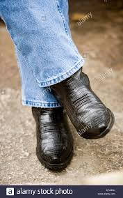 close up of a man u0027s feet in blue jeans and cowboy boots stock