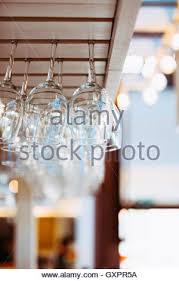 empty wine glasses hanging above the bar counter stock photo