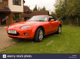mazda sports car a red mazda mx5 sports car parked on a drive outside a house stock
