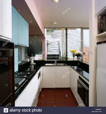 black worktops in modern kitchen with pale blue and white fitted
