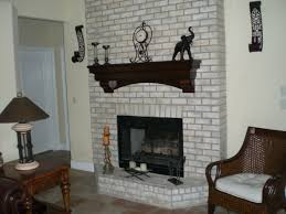 white brick fireplace with black mental fire box and black wooden