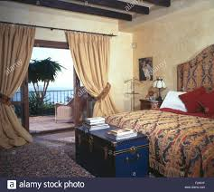 blue chest below bed in spanish bedroom with cream curtains on