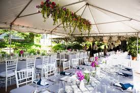 tent wedding decorations simple wooden chairs over grees grass