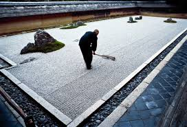 apprentice monk rakes the garden at ryoanji a zen temple in kyoto