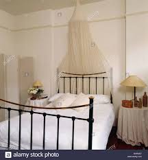 white mosquito net above black wrought iron bed with white