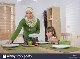 arab mother and daughter in the dining room woman setting table