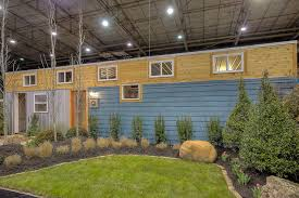 the container home is clad in lap siding with a rim of cedar and