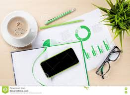 office desk with charts coffee plant and phone stock photo