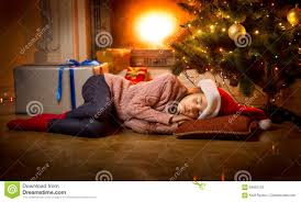 sleeping on floor under christmas tree next to fireplace