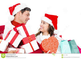 happy couple with santa hats holding gift boxes and shopping bags