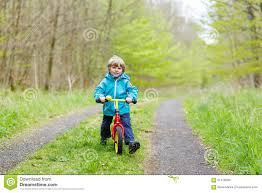 bike raincoat little kid boy riding on a bike in forest stock photo image