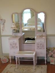 beautiful pink antique vanity with tri fold mirror and cane bench