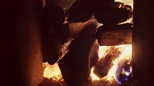 a large pile of firewood burning in a brick fireplace the flames