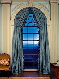 in this living room dramatic floor to ceiling arched windows