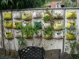 recycled plastic planter bags hanging on the wire fence backyard