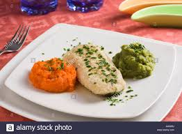 hake filet with carrots and broccolis purees in an elegant dinner