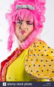 yellow with pink polka dots man dressed as female panto dame pouts for the camera with pink wig