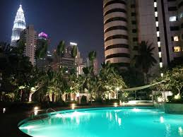 pool view looking at one of the petronas twin towers at night from