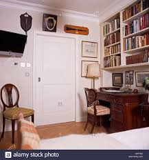 television on wall beside door in traditional study bedroom with